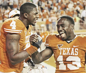 Photo - Texas wide receiver Dan Buckner, left, had five catches for 62 yards in the Longhorns' opener.AP photo