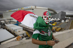Photo - Backdropped by the Itaquerao stadium, a Mexico soccer fan poses for a photo wearing a wrestling mask and a representation of his country's national flag as a cape, in Sao Paulo, Brazil, Tuesday, June 10, 2014. The high-profile inaugural match will be played at the troubled Itaquerao, which was one of the most delayed venues for the World Cup. It's already known that the stadium's roof won't be fully finished until after the tournament. (AP Photo/Eduardo Verdugo)