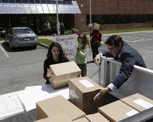 Photo - Jessica Azulay of Alliance for a Green Economy, left, and Keith Schue of Sustainable Otsego unload boxes of comments at the New York State Energy Research and Development Authority offices on Friday, May 30, 2014, in Albany, N.Y. The comments, filed on the deadline for responding to the draft state energy plan issued in January, urge New York officials to reject additional natural gas drilling as any sort of environmental solution, calling instead for a much stronger push for renewable and cleaner solar and wind power. (AP Photo/Mike Groll)