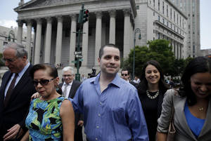 Photo - GIlberto Valle, center, leaves Manhattan federal court in New York on Tuesday, July 1, 2014. A federal judge overturned the conviction of the former New York City police officer accused of plotting to kidnap, kill and eat young women. (AP Photo/Seth Weng)