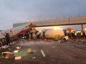 photo - Rescuers work at the site of careered off the runway plane at Vnukovo Airport in Moscow, Saturday, Dec. 29, 2012. A Tu-204 aircraft belonging to Russian airline Red Wings careered off the runway at Russia's third-busiest airport on Saturday, broke into pieces and caught fire, killing several people. (AP Photo/Alexander Usoltsev)