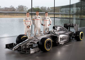 Photo - This photo provided Friday Jan. 24, 2014 by McLaren shows the new MP4-29 with drivers Kevin Magnussen of Denmark, left, Jenson Button of Britain, center, and Stoffel Vandoorne of Belgium at the McLaren Technology Centre in Woking, England. (AP Photo/McLaren)