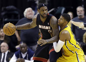 Photo - Miami Heat forward LeBron James, left, is defended by Indiana Pacers forward Paul George in the second half of an NBA basketball game in Indianapolis, Tuesday, Dec. 10, 2013. The Pacers won 90-84. (AP Photo/Michael Conroy)