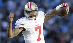 Photo - San Francisco 49ers quarterback Colin Kaepernick (7) runs against the Carolina Panthers during the second half of a divisional playoff NFL football game, Sunday, Jan. 12, 2014, in Charlotte, N.C. (AP Photo/Gerry Broome)