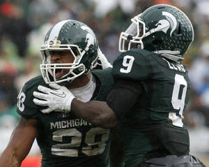 Photo - Michigan State's Denicos Allen, left, and Isaiah Lewis celebrate a stop by Allen against Michigan during the second quarter of an NCAA college football game, Saturday, Nov. 2, 2013, in East Lansing, Mich. (AP Photo/Al Goldis)