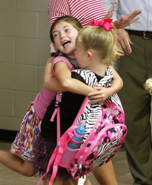 Photo - First-graders Reaghan White, left, and Bella Leding enjoy seeing each other as classes begin Tuesday at  Frontier Elementary School, in the Edmond, Oklahoma, school district. Tuesday, August 20, 2013,  Photo by Paul Hellstern, The Oklahoman