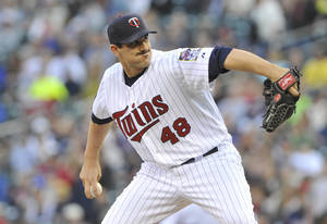 Photo - FILE - This  May 9, 2012 file photo shows Minnesota Twins pitcher Carl Pavano in a baseball game against the Los Angeles Angels in Minneapolis. Pavano announced in a statement released Wednesday, Feb. 26, 2014, that he is retiring after 14 major league seasons. (AP Photo/Jim Mone, file)