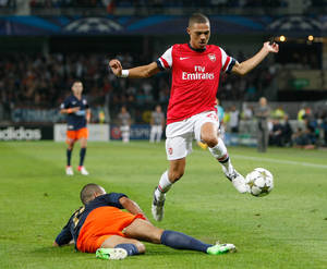 Photo -   Arsenal's defender Kieran Gibbs from Britain, right, challenges for the ball with Montpellier's French defender Garry Bocaly, during the Champions League Group B soccer match between Montpellier and Arsenal, at the La Mosson stadium, in Montpellier, southern France, Tuesday, Sept.18, 2012. (AP Photo/Claude Paris)