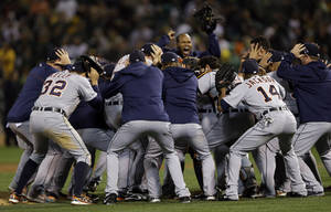Photo - The Detroit Tigers celebrate after beating the Oakland Athletics 3-0 in to win Game 5 of an American League baseball division series in Oakland, Calif., Thursday, Oct. 10, 2013. (AP Photo/Marcio Jose Sanchez)