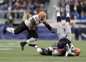 Photo - Cleveland Browns safety T.J. Ward (43) and linebacker D'Qwell Jackson (52) tackle New England Patriots tight end Rob Gronkowski (87) after a catch in the third quarter of an NFL football game Sunday, Dec. 8, 2013, in Foxborough, Mass. (AP Photo/Steven Senne)