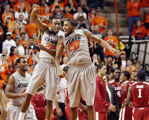 photo - OSU's Markel Brown (22) and Michael Cobbins (20) celebrate a dunk by Brown in the second half during the Bedlam men's college basketball game between the Oklahoma State University Cowboys and the University of Oklahoma Sooners at Gallagher-Iba Arena in Stillwater, Okla., Monday, Jan. 9, 2012. At left is OSU's Brian Williams (4). OSU beat OU, 72-65. Photo by Nate Billings, The Oklahoman