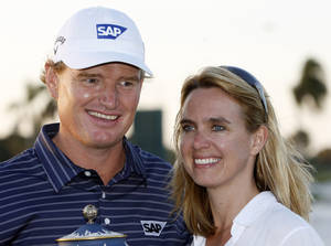 Photo - File - in this Sunday, March 14, 2010 file photo. Ernie Els and his wife Lieztl pose for photographers during the trophy ceremony at the CA Championship golf tournament in Doral, Fla. Els says he is considering cutting his golf schedule even more to spend time with his family, it was announced on Thursday, Dec. 5, 2103. The four-time major winner has already slowed down over the past few years, playing 19 tournaments on the PGA Tour and only seven European Tour events last season. (AP Photo/Alan Diaz, File)