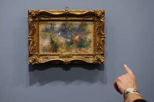 "Photo - A woman points at details in Pierre-Auguste Renoir's painting ""On the Shore of the Seine"" after a news conference at the Baltimore Museum of Art in Baltimore, Thursday, March 27, 2014, more than 60 years after it was stolen from the museum. The painting became the subject of a dramatic legal dispute after a Virginia woman claimed she bought it at a flea market for $7. A judge ultimately awarded ownership back to the Baltimore museum, and it is scheduled to go on public display March 30. (AP Photo/Patrick Semansky)"