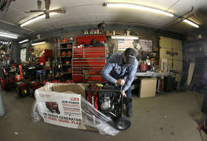 photo - Chris Oppenberg of Andover Small Engine Service assembles a home generator for a customer in Andover, Mass., Thursday, Feb. 7, 2013, in preparation for a major winter storm headed toward the U.S. Northeast. The National Weather Service calls for up to 2 feet of snow expected for a Boston-area region that has seen mostly bare ground this winter. (AP Photo/Elise Amendola)