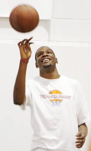 Photo - Kevin Durant, left, spins a basketball during Kevin Durant Basketball Camp on Thursday, July 1, 2010, at Heritage Hall School in Oklahoma City. Photo by Nate Billings, The Oklahoman.
