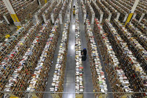 Photo -  An Amazon.com employee stocks books along one of the many miles of aisles at an Amazon.com Fulfillment Center in Phoenix.  AP Photo  <strong>Ross D. Franklin -  AP </strong>