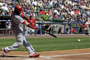Photo - Cincinnati Reds' Brandon Phillips hits a two-RBI single during the second inning of a baseball game against the Milwaukee Brewers, Sunday, Aug. 18, 2013, in Milwaukee. (AP Photo/Morry Gash)