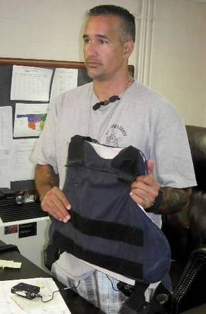 photo - Pottawatomie County sheriff's deputy Joe Leeds holds the bulletproof vest that kept him from harm.  Photo provided