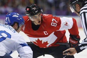 Photo - Canada forward Sidney Crosby watches the official during a face-off against Finland forward Jarkko Immonen in the first period of a men's ice hockey game at the 2014 Winter Olympics, Sunday, Feb. 16, 2014, in Sochi, Russia. (AP Photo/Mark Humphrey)