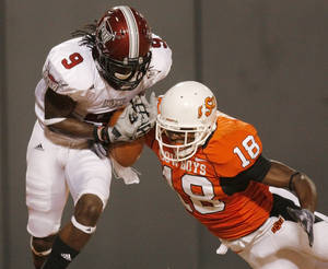 Photo - OSU's Devin Hedgepeth (18) breaks up a pass in the end zone intended for Jason Bruce (9) of Troy in the third quarter during the college football game between the Oklahoma State University Cowboys (OSU) and the Troy University Trojans at Boone Pickens Stadium in Stillwater, Okla., Saturday, Sept. 11, 2010. OSU won, 41-38. Photo by Nate Billings, The Oklahoman