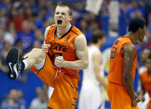 Photo - Oklahoma State's Phil Forte celebrates defeating Kansas in an NCAA college basketball game in Lawrence, Kan. on Saturday, Feb. 2, 2013. (AP Photo/The Wichita Eagle, Travis Heying)  ORG XMIT: KSWIE101
