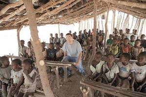 photo - 1040i?s media specialist Jacob Meyer, center, sits with a group of Ivory Coast children in a makeshift school, far away from the country?s bigger cities. PHOTO PROVIDED