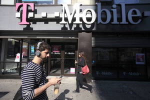 Photo - FILE - This Sept. 12, 2012 file photo shows a man using a cellphone as he passes a T-Mobile store in New York. T-Mobile USA knowingly made hundreds of millions off its customers in bogus charges, a federal regulator alleged Tuesday in a complaint that is likely to damage the reputation of a household name in wireless communications. In its complaint filed in federal court, the Federal Trade Commission claimed that T-Mobile billed consumers for subscriptions to premium text services such as $10-per-month horoscopes that were never authorized by the account holder. The FTC alleges that T-Mobile collected as much as 40 percent of the charges, even after being alerted by other customers that the subscriptions were scams. (AP Photo/Mark Lennihan, File)