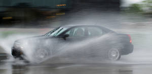 Photo - Cars go through standing water on Classen Boulevard near The Curve shopping center Monday. <strong>DOUG HOKE - THE OKLAHOMAN</strong>