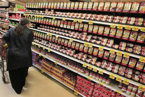 Photo - FILE - This Feb. 7, 2012 file photo shows a shopper walking down the canned soup aisle at a grocery store in Cincinnati. Food companies and restaurants could soon face government pressure to make their foods less salty _ a long-awaited federal effort to try and prevent thousands of deaths each year from heart disease and stroke.  (AP Photo/Al Behrman, File)