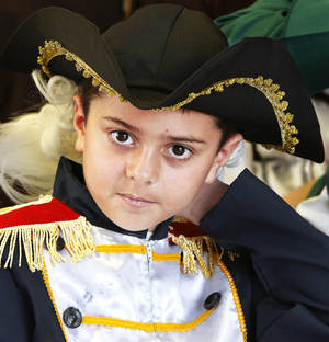 photo - Above: Lane Youngblood wears a white wig for his role as Gen. George Washington on Wednesday at Schwartz Elementary School.