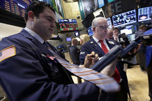Photo - Traders work on the floor of the New York Stock Exchange Monday, Dec. 16, 2013. U.S. stocks rose sharply on Monday, powered by two big corporate deals and news that suggests the economy is getting stronger. (AP Photo/Richard Drew)