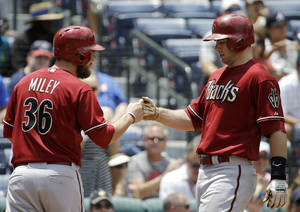 Photo - Arizona Diamondbacks' Paul Goldschmidt, right, fist-bumps teammate Wade Miley after hitting a two-run home run to score them in the third inning of a baseball game against the Atlanta Braves, Sunday, July 6, 2014, in Atlanta. (AP Photo/David Goldman)