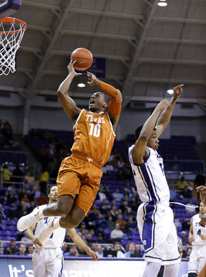 Photo - Texas forward Jonathan Holmes gets past TCU forward Brandon Parrish (11) to take a shot during the first half of an NCAA college basketball game Tuesday, Feb. 4, 2014, in Fort Worth, Texas. (AP Photo/Sharon Ellman)