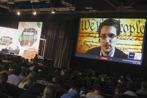 Photo - Edward Snowden talks during a simulcast conversation during the SXSW Interactive Festival on Monday, March 10, 2014, in Austin, Texas. Snowden talked with American Civil Liberties Union's principal technologist Christopher Soghoian, and answered tweeted questions. (Photo by Jack Plunkett/Invision/AP)