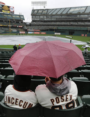 Photo - San Francisco Giants fans wait under an umbrella before a spring exhibition baseball game between the Giants and the Oakland Athletics, Saturday, March 29, 2014, in Oakland, Calif. (AP Photo/Ben Margot)