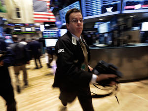 Photo - Trader Joseph Murray rushes across the floor of the New York Stock Exchange Wednesday, Oct. 9, 2013. Stocks are wavering between small gains and losses in early trading as US companies report mixed earnings news. (AP Photo/Richard Drew)