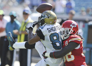 Photo - Jacksonville Jaguars wide receiver Cecil Shorts, left, makes a reception despite a defensive effort by Kansas City Chiefs defensive back Ron Parker, right, during the second half of an NFL football game in Jacksonville, Fla., Sunday, Sept. 8, 2013. Kansas City Chiefs won the game 28-2.(AP Photo/Stephen Morton)