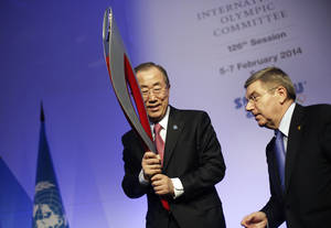 Photo - United Nations Secretary-General Ban Ki-moon, left, is handed an Olympic torch by International Olympic Committee President Thomas Bach after Ban addressed the IOC general assembly ahead of the upcoming 2014 Winter Olympics, Thursday, Feb. 6, 2014, in Sochi, Russia. It was the first time a U.N. secretary-general delivered a keynote address to the IOC's general assembly. (AP Photo/David Goldman)