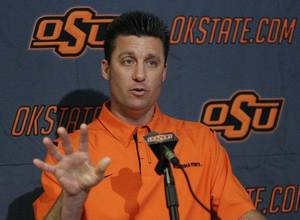 Photo - Oklahoma State head football coach Mike Gundy gestures as he answers a question during an NCAA college football news conference on national signing day in Stillwater, Okla., Wednesday, Feb. 3, 2010. (AP Photo/Sue Ogrocki)