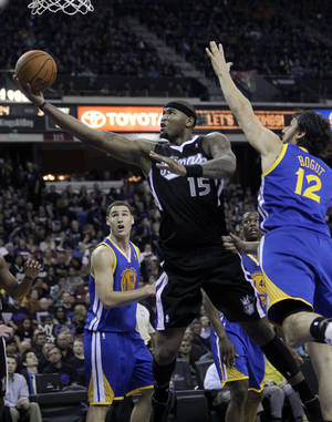 Photo -   Sacramento Kings center DeMarcus Cousins, center, drives to the basket between Golden State Warriors' Klay Thompson, left, and Andrew Bogut, of Australia, during the second half of an NBA basketball game in Sacramento, Calif., Monday, Nov. 5, 2012. The Kings won 94-92.(AP Photo/Rich Pedroncelli)