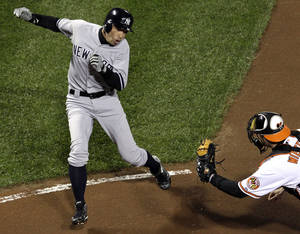 Photo -   New York Yankees' Ichiro Suzuki, left, of Japan, runs past Baltimore Orioles catcher Matt Wieters to score a run on a double by Robinson Cano in the first inning of Game 2 of the American League division baseball series on Monday, Oct. 8, 2012, in Baltimore. (AP Photo/Patrick Semansky)