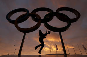 Photo - A woman poses for with the Olympic rings in Olympic Park as preparations continue for the 2014 Winter Olympics, Wednesday, Feb. 5, 2014, in Sochi, Russia. (AP Photo/Charlie Riedel)