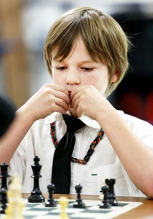 Photo - Ashton Pavao, 3rd grade, studies his chess move during a chess club meeting at Freeman Elementary School in Edmond, Tuesday December 12, 2012. Photo By Steve Gooch, The Oklahoman