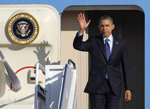 Photo - President Barack Obama waves as he walks off Air Force One at Andrews Air Force Base, Md., Thursday, Feb. 14, 2013, upon returning from Decatur, Ga., where he spoke of his education plans., following his State of the Union address.  (AP Photo/Ann Heisenfelt)