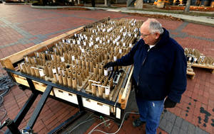 Photo - Vernon Muzny checks some of the 1500 shells set up across the street from the Myriad Gardens for Opening Night on Tuesday, Dec. 31, 2013, in Oklahoma City, Okla.  Western Enterprises from Carrier, Okla. is responsible for the fireworks.  Photo by Steve Sisney, The Oklahoman