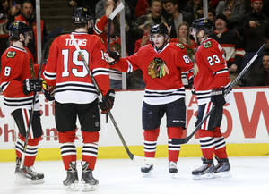 Photo - Chicago Blackhawks right wing Patrick Kane (88) celebrates his goal with Nick Leddy (8), Jonathan Toews (19) and Kris Versteeg (23) during the second period of an NHL hockey game against the New Jersey Devils, Monday, Dec. 23, 2013, in Chicago. (AP Photo/Charles Rex Arbogast)