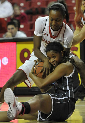 Photo - Delaware State's Raven Bankston, bottom, and  Maryland's Shatori Walker-Kimbrough struggle for a loose ball in the first half of an NCAA college basketball game on Saturday, Dec. 14, 2013, in College Park, Md.(AP Photo/Gail Burton)