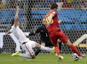 Photo - Belgium's Daniel Van Buyten, right, shoots as United States' Matt Besler, left,  tries to block during the World Cup round of 16 soccer match between Belgium and the USA at the Arena Fonte Nova in Salvador, Brazil, Tuesday, July 1, 2014. (AP Photo/Felipe Dana)