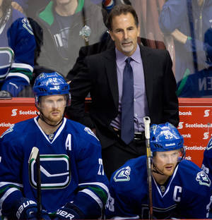 Photo - Vancouver Canucks' head coach John Tortorella, top, stands on the bench as Daniel Sedin, left, and his twin brother Henrik Sedin, both of Sweden, watch the play during third period NHL hockey action against the Boston Bruins in Vancouver, British Columbia, on Saturday, Dec. 14, 2013. (AP Photo/The Canadian Press, Darryl Dyck)