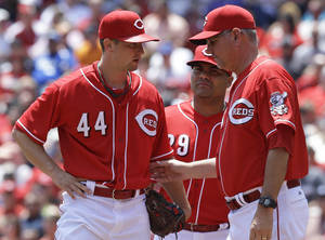 Photo - Cincinnati Reds starting pitcher Mike Leake (44) talks with pitching coach Jeff Pico, right, as first baseman Brayan Pena listens in, during the fourth inning of a baseball game against the San Francisco Giants, Thursday, June 5, 2014, in Cincinnati.  (AP Photo/Al Behrman)